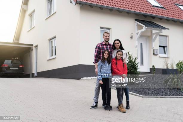 portrait of parents and twin daughters in front of their family home - middle class stock pictures, royalty-free photos & images