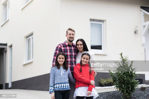 Portrait of parents and twin daughters in front of their family home