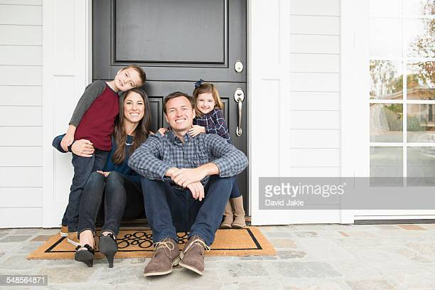 Portrait of parents and two children sitting at front door