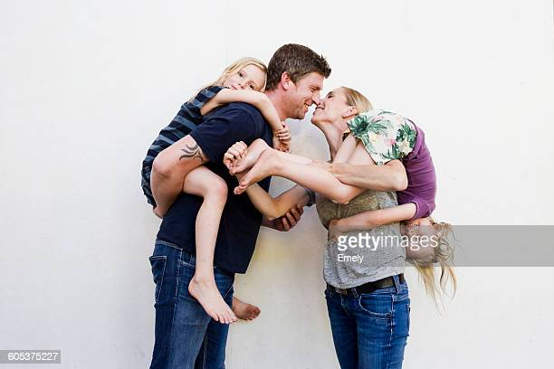 portrait of parents carrying two young daughters in front of white wall - couple calin photos et images de collection