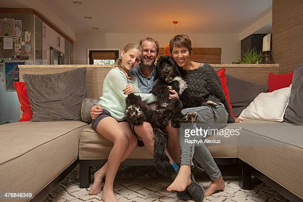 portrait of parents, daughter and pet dog on sofa - hairy little girls stock photos and pictures