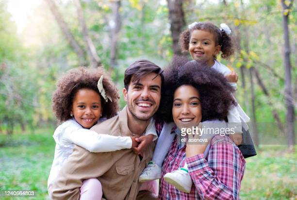 portret van ouders die kinderen piggybacks geven - gemengde afkomst stockfoto's en -beelden