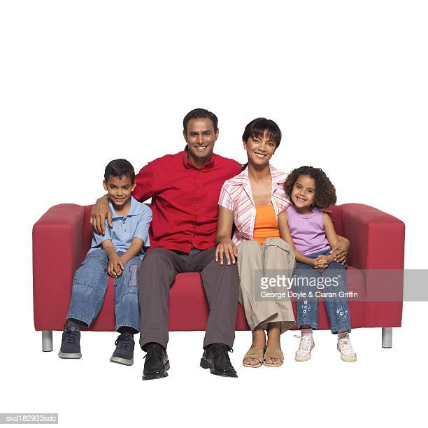 Portrait of parents sitting on sofa with their son (10-11) and daughter (8-9)