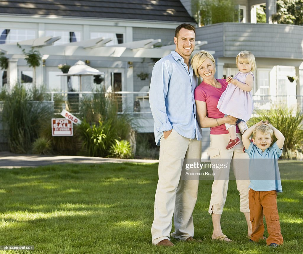 Portrait of parents with baby girl (9-12 months) and son (2-3) in front of Sold House : Foto stock