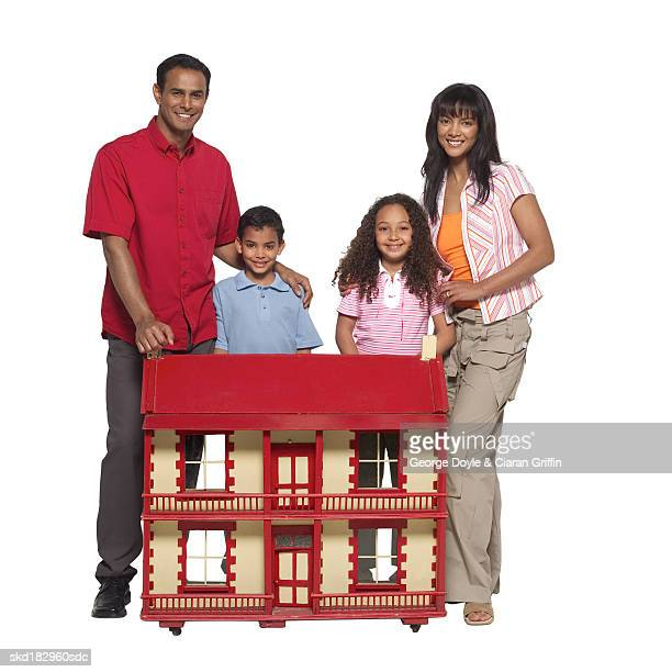Portrait of parents with their daughter (11-12) and son (10-11) standing with a dolls house