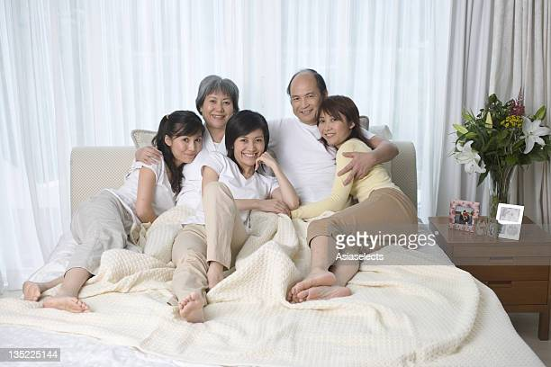 portrait of parents with their three daughters on the bed - soles pose stockfoto's en -beelden