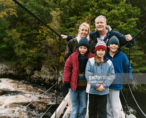 portrait of parents with three young children standing on a footbridge over a river - five people stock pictures, royalty-free photos & images