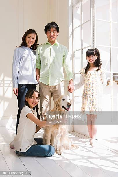 Portrait of parents with two girls (8-11) and dog in home