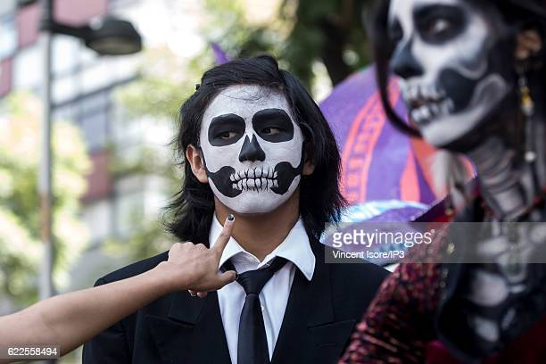 Portrait of participants who wear colorful costumes and parade through the streets during the 'Catrinas Parade' a joyful annual event celebrated at...