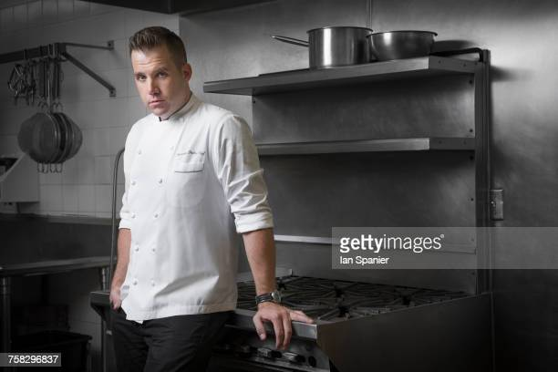 Portrait of pastry chef leaning against hob in kitchen