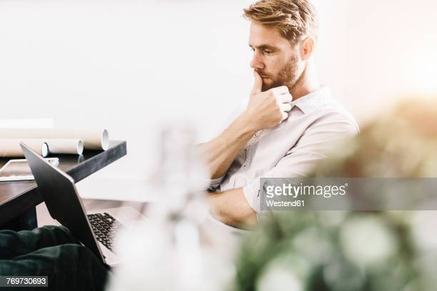 Portrait of pensive architect sitting with feet up at desk looking at laptop