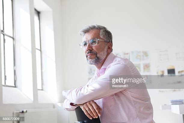 portrait of pensive businessman sitting in an office - da cintura para cima imagens e fotografias de stock