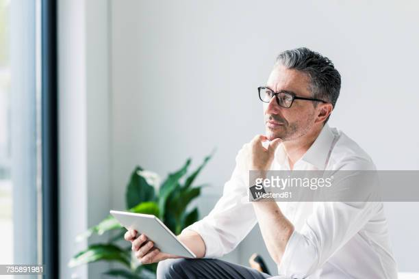 Portrait of pensive businessman with tablet and smartwatch