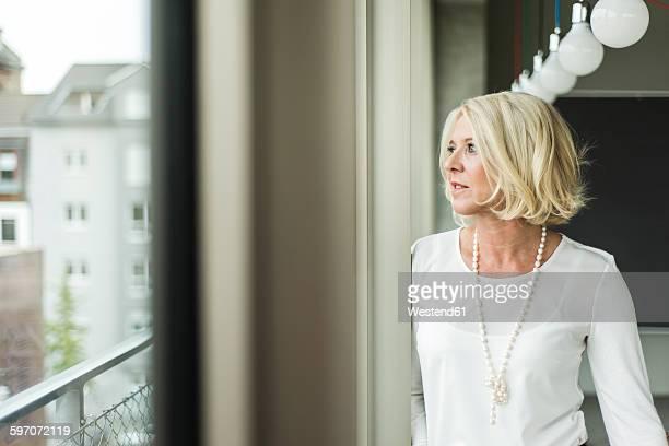 Portrait of pensive businesswoman looking through window