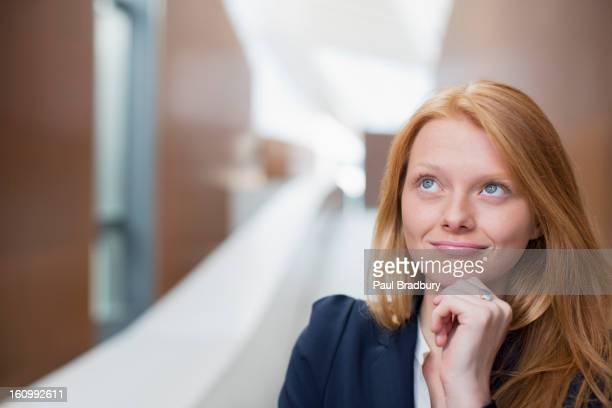 Portrait of pensive businesswoman looking up
