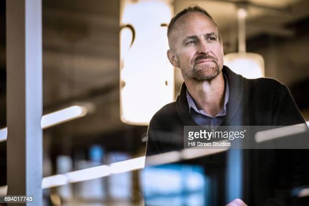 Portrait of pensive Caucasian man behind window