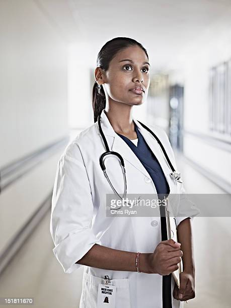 portrait of pensive doctor holding medical record in hospital corridor - three quarter length stock pictures, royalty-free photos & images