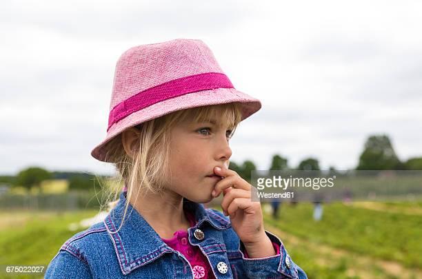 Portrait of pensive little girl wearing pink hat on a strawberry field