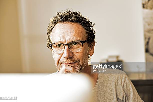 Portrait of pensive man looking at computer