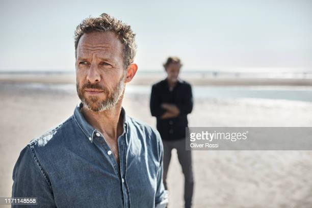 portrait of pensive man on the beach - introspektion stock-fotos und bilder