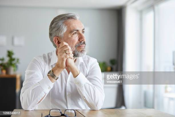 portrait of pensive mature man  at home - looking away stock pictures, royalty-free photos & images