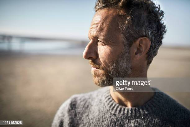 portrait of pensive mature man on the beach - serious stock pictures, royalty-free photos & images