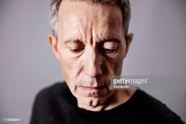 portrait of pensive mature man - blick nach unten stock-fotos und bilder