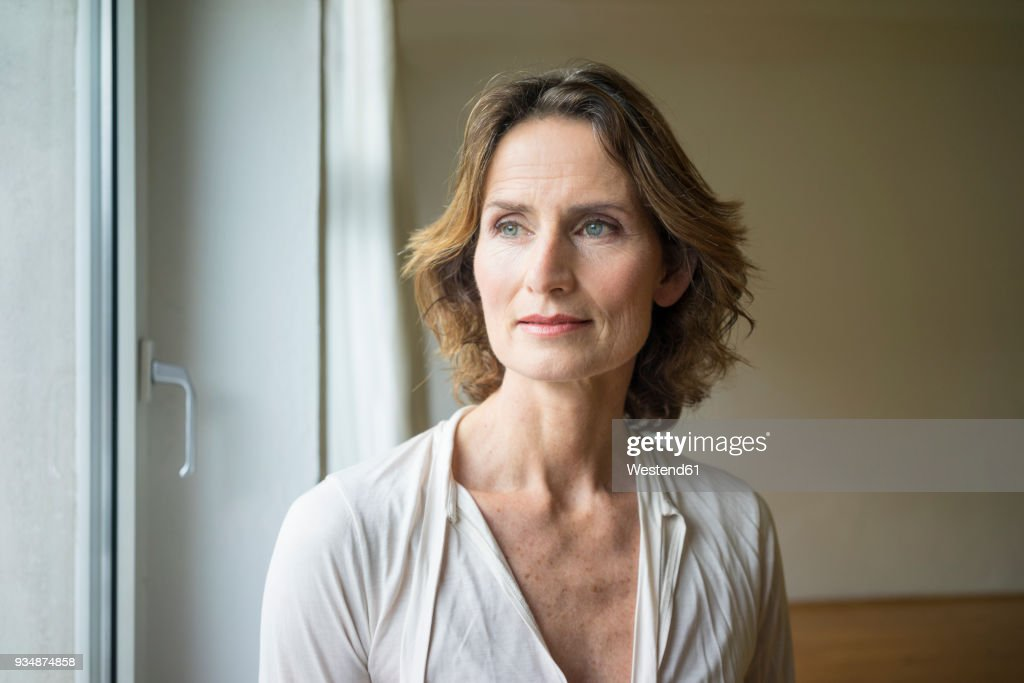 Portrait of pensive mature woman at the window : Stockfoto