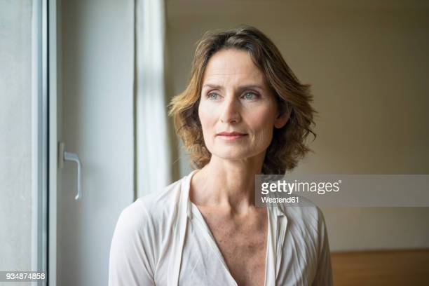 portrait of pensive mature woman at the window - mulheres maduras imagens e fotografias de stock