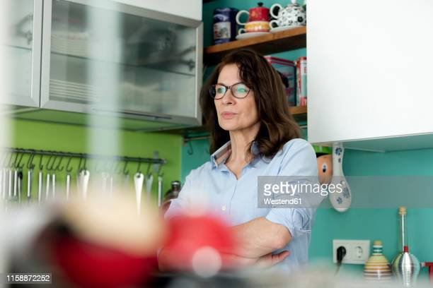 portrait of pensive mature woman in kitchen at home - stay at home mother stock pictures, royalty-free photos & images