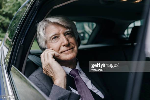 portrait of pensive senior businessman looking through car window - white hair stock photos and pictures