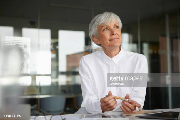 portrait of pensive senior businesswoman at desk in her office - 60 64 jahre stock-fotos und bilder