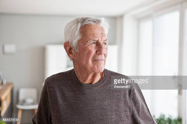 portrait of pensive senior man at home - wegkijken stockfoto's en -beelden