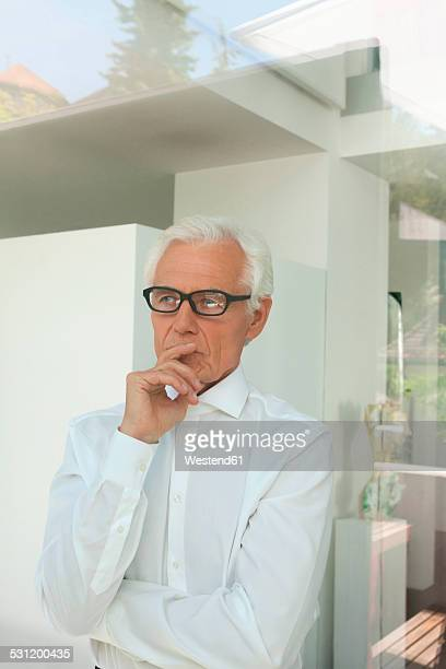 Portrait of pensive senior man looking out of a window