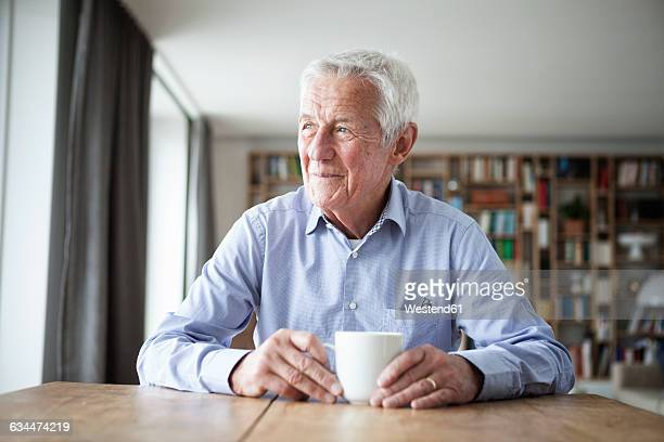 Portrait of pensive senior man sitting at table with cup of coffee looking through window
