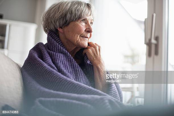 Portrait of pensive senior woman sitting on couch at home