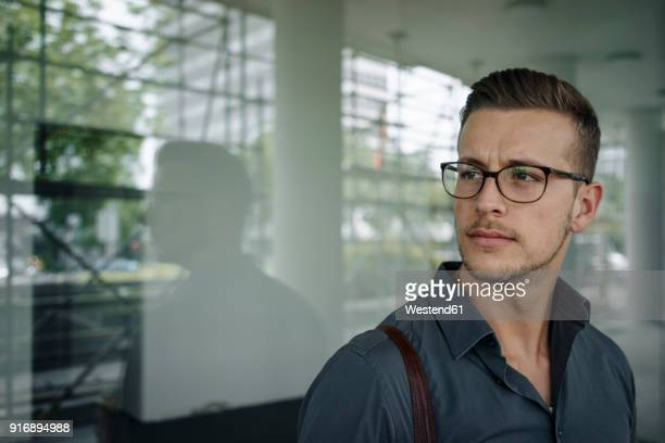 Portrait of pensive young businessman wearing glasses