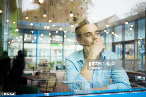 Portrait of pensive young man sitting in a coffee shop looking through window
