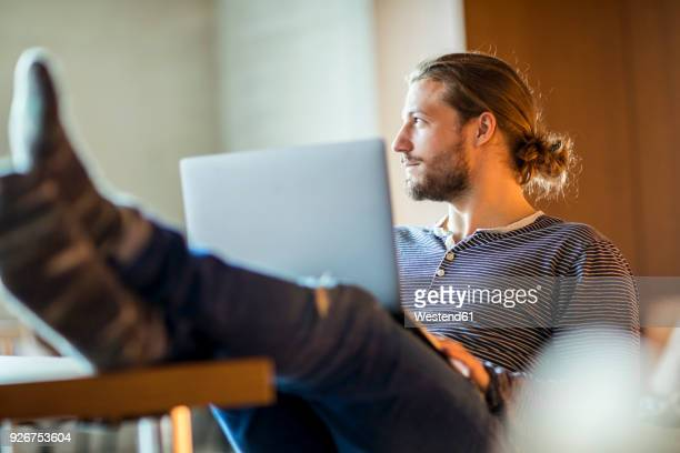 portrait of pensive young man using laptop - gelassene person stock-fotos und bilder