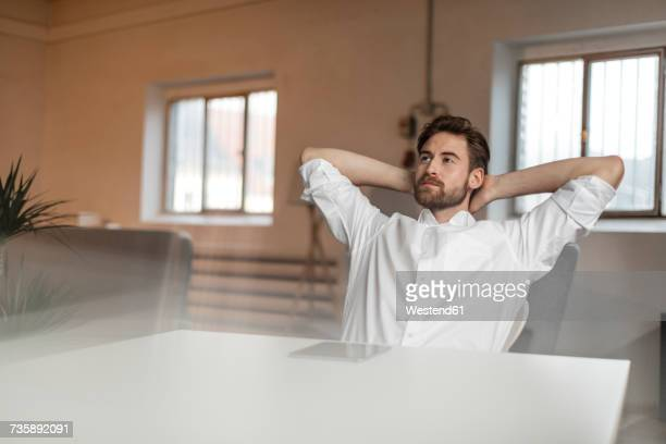 Portrait of pensive young man with hands behind head sitting at table