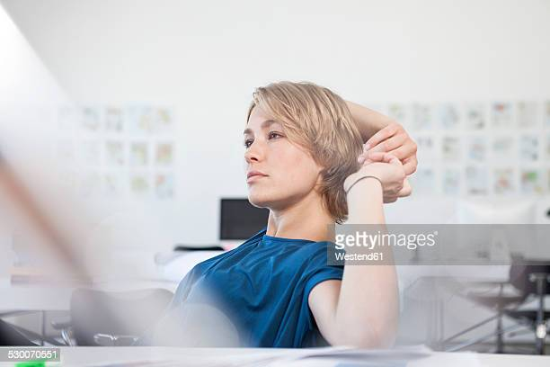 Portrait of pensive young woman at her desk in a creative office