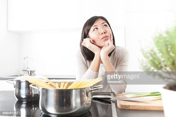 portrait of pensive young woman cooking spaghetti - electric stove burner stock pictures, royalty-free photos & images