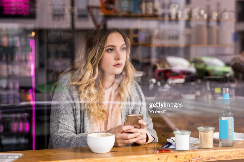 Portrait of pensive young woman in a coffee shop looking through window : Stock Photo