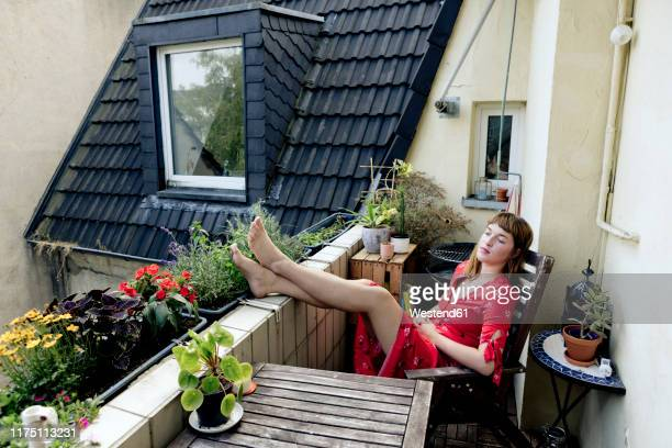 portrait of pensive young woman relaxing with feet up on balcony - balcony stock pictures, royalty-free photos & images