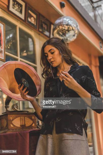 Portrait of pensive young woman standing in front of antique shop holding gramophone record
