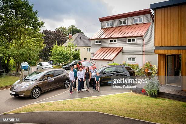 Portrait of people in neighbourhood with electric cars