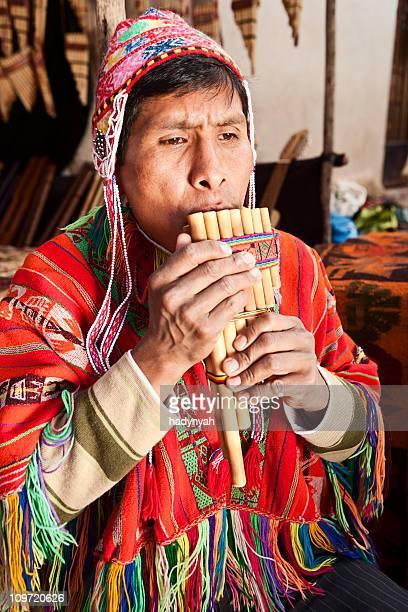 Portrait of Peruvian man playing a siku (panpipe), Pisac market