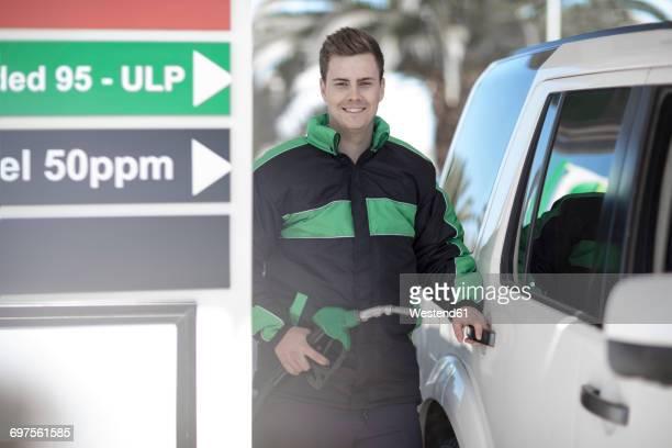 Portrait of petrol attendant fueling car