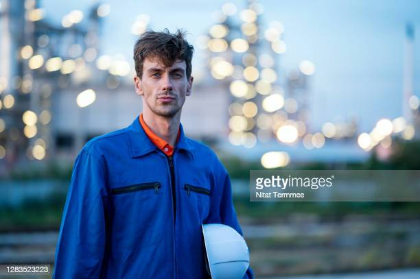 portrait of petroleum engineer wearing protective workwear coveralls at oil and gas refinery facility. - vaseline imagens e fotografias de stock