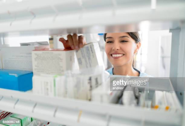 Portrait of pharmacist looking for prescribed medications in the cabinet